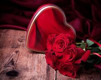 Gift box and bouquet of roses on wooden background Stock Photography