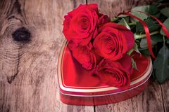Gift box and bouquet of roses on wooden background Royalty Free Stock Images