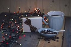 Gift box with bow, blue cup, coffee beans on Christmas tablenn Royalty Free Stock Image