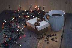 Gift box with bow, blue cup, lights, coffee grains on tablenn Royalty Free Stock Image