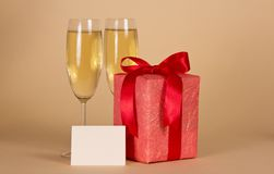 Gift box with a bow, empty card and wine glasses Royalty Free Stock Image