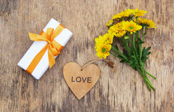 Gift box with a bow, flowers and a wooden heart. Romantic concept. Royalty Free Stock Photo