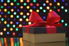 Gift box with a bow in front of a festive garland lights background Royalty Free Stock Photo