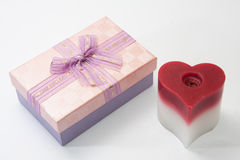 Gift box with bow and heart candle Stock Images