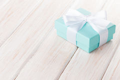 Gift box with bow over white wooden table Royalty Free Stock Photos