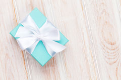Gift box with bow over white wooden table Royalty Free Stock Image