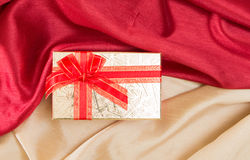 Gift box with bow, on red and golden wavy fabrics. Royalty Free Stock Photos