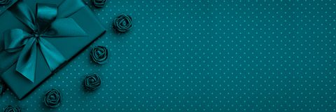 Gift box with bow and ribbon, flower rose top view on dark blue or turquoise background. Flat lay. Top View. 8 march Womens Day. Birthday, Valentines Day stock image