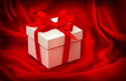 Gift box with bow ribbon on red silk Stock Image