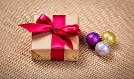 Gift box with a bow and shiny Christmas balls. Festive concert. Stock Images
