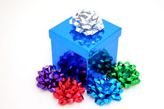 Gift box and bows. A sparkling blue gift box with multi colored bows Stock Photo