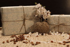 Gift in the box and a branch of a flowering tree. Gift in a box and a branch of a flowering tree on a burlap with coffee beans stock photo