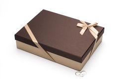 The gift box with a brown cover also is wrapped up by a yellow tape with a bow with a heart For you. Royalty Free Stock Photography