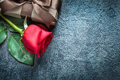 Gift box with brown ribbon red rose on black background holidays Stock Photo