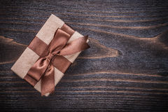 Gift box with brown tied bow on vintage wooden board Stock Photography