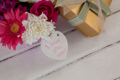 Gift box and bunch of fresh flowers with I love you mom card Royalty Free Stock Image