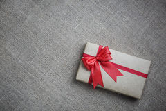 Gift in a box on the burlap Royalty Free Stock Images