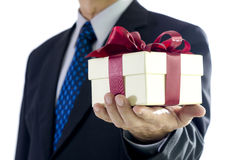 Gift Box. Business man holding a gift box on white background Royalty Free Stock Photos