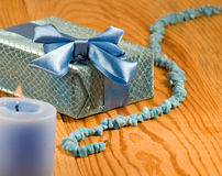 Gift box, candle and beads on table Stock Photos