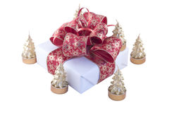 Gift box and candles. Beautifully packed gift box with xmas tree-shaped candles Stock Photo