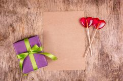Gift box and candy hearts. Romantic concept. Lollipops on heart shaped stick and box with ribbon. Stock Photos