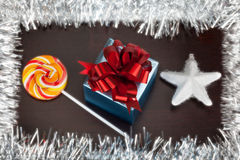 Gift box, candycane and white christmas star on black wood Stock Images