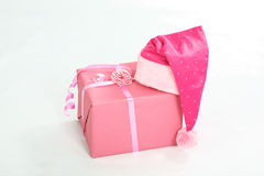 Gift box with cap. Purple Santa cap on the pink gift box on white background Stock Image