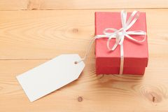 Gift box with card on wooden background Royalty Free Stock Photos