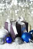 Gift box with christmas ball on snow, close up Royalty Free Stock Image