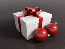 Gift box with christmas balls and a red ribbon. On a black wooden floor Stock Photography