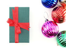 green gift box with red ribbon bow and pile of colorful glossy christmas balls isolated on white background Royalty Free Stock Images