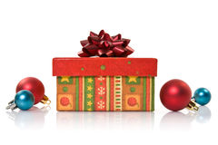 Gift box and christmas baubles Stock Photography