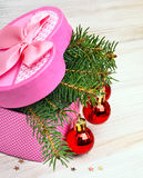 Gift box with christmas baubles and pinetree. On a wooden background Stock Photography