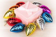 Gift box and Christmas decorations in form of fir cones Royalty Free Stock Images