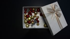 Gift box with Christmas globes inside against dark background royalty free stock photos