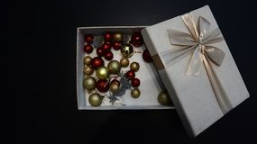 Gift box with Christmas globes inside against dark background royalty free stock images