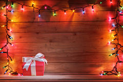 Gift box with christmas light and wooden background. Stock Photography
