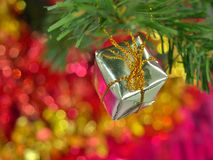 Gift box Christmas ornament on pine tree branch. Stock Photo