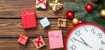 Gift box and clock with christmas baubles Stock Photos