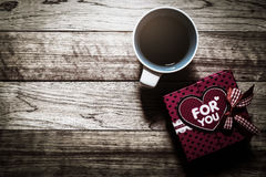 Gift box and coffee on wooden plank Royalty Free Stock Photo
