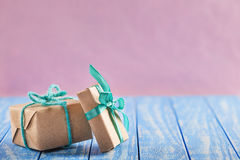 Gift box in craft paper on a wooden table pink background Stock Photo