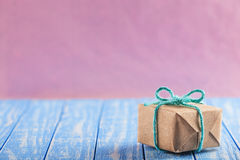 Gift box in craft paper on a wooden table pink background Stock Photography