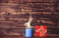 Gift box and cup of coffee Stock Images