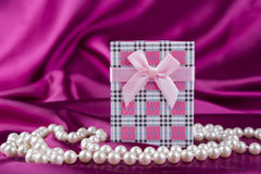 Gift box on curvy satin fabric background with pearl necklace Stock Photo
