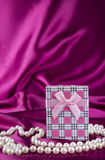 Gift box on curvy satin fabric background with pearl necklace Royalty Free Stock Images