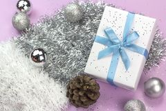 Gift box decorated with bright blue ribbon on silver tinsel and royalty free stock photo