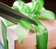 Decorating gift box with green ribbon using scissor Stock Photo