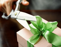 Decorating gift box with green ribbon using scissor Royalty Free Stock Photos