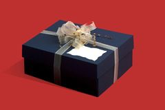 Gift box with decorative bow  on red. Background Royalty Free Stock Image
