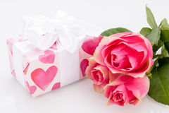 Gift box with an empty tag, next to three roses Stock Image